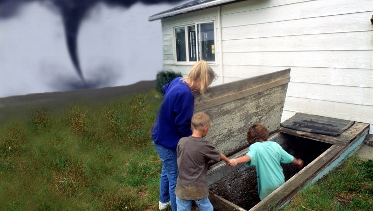 A family enters a storm cellar while a tornado touches down in the background.